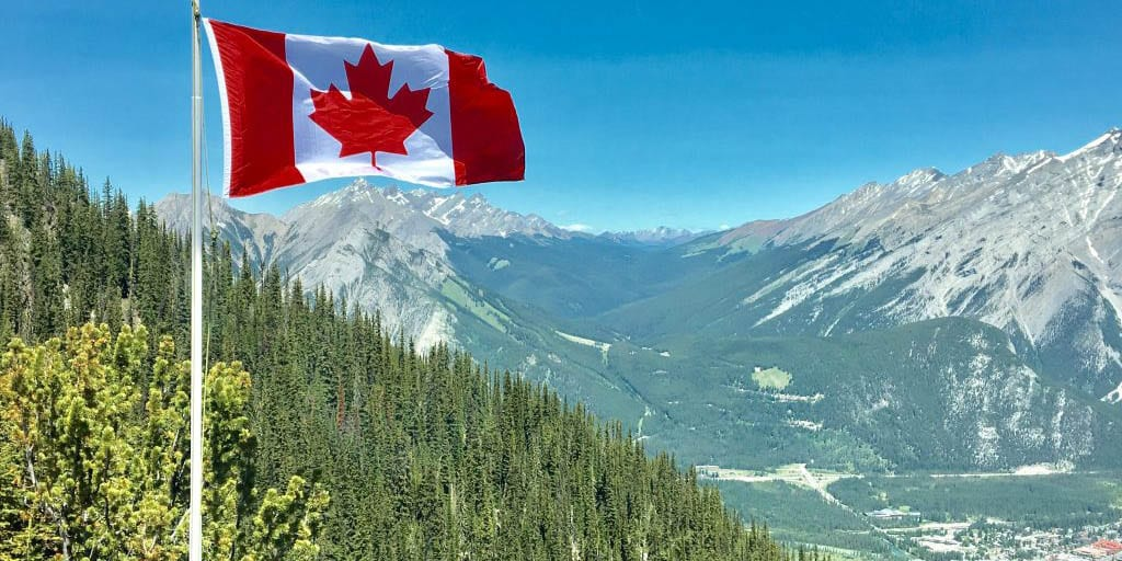 Flag of Canada in front of mountains